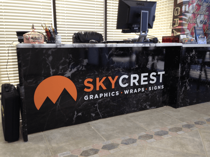 particle board desk wrapped in marble design with logo